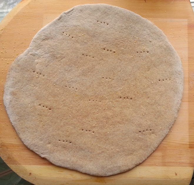 rolled pizza dough on a wooden peel